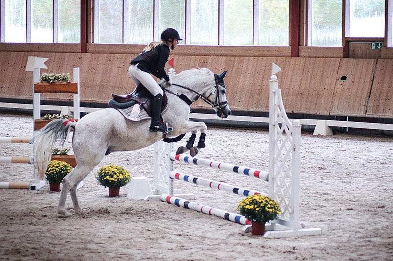 Mädchen auf Pferd beim Sprung über Hindernis in Reithalle