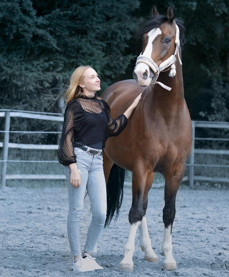 Frau stehend neben Pferd auf Koppel mit Hand auf Pferderücken